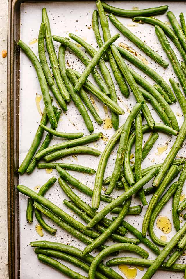 Fresh green beans on a baking sheet.
