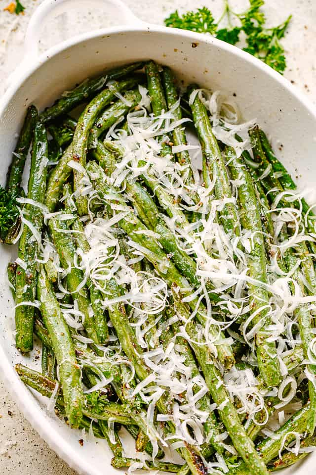 Green Beans served in a white dish and topped with fresh parmesan cheese.