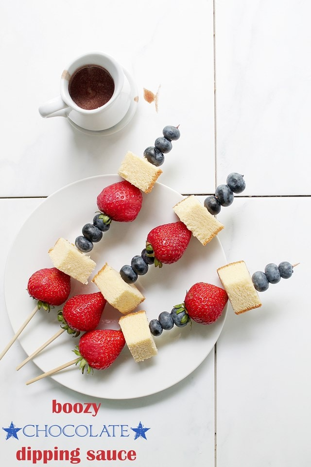 Top view of strawberries, blueberries and pound cake on skewers on a white plate with chocolate sauce next to it