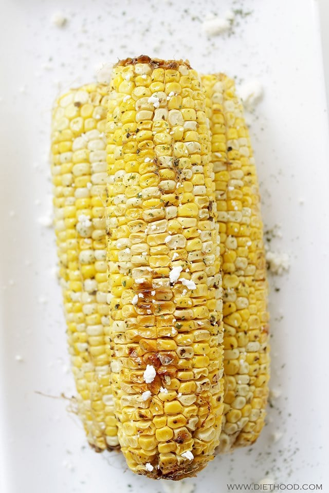 3 ears of grilled corn served on a white plate