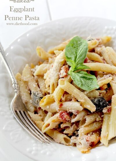 A close up of penne pasta in a white bowl with tomatoes, cheese, eggplant and topped with basil