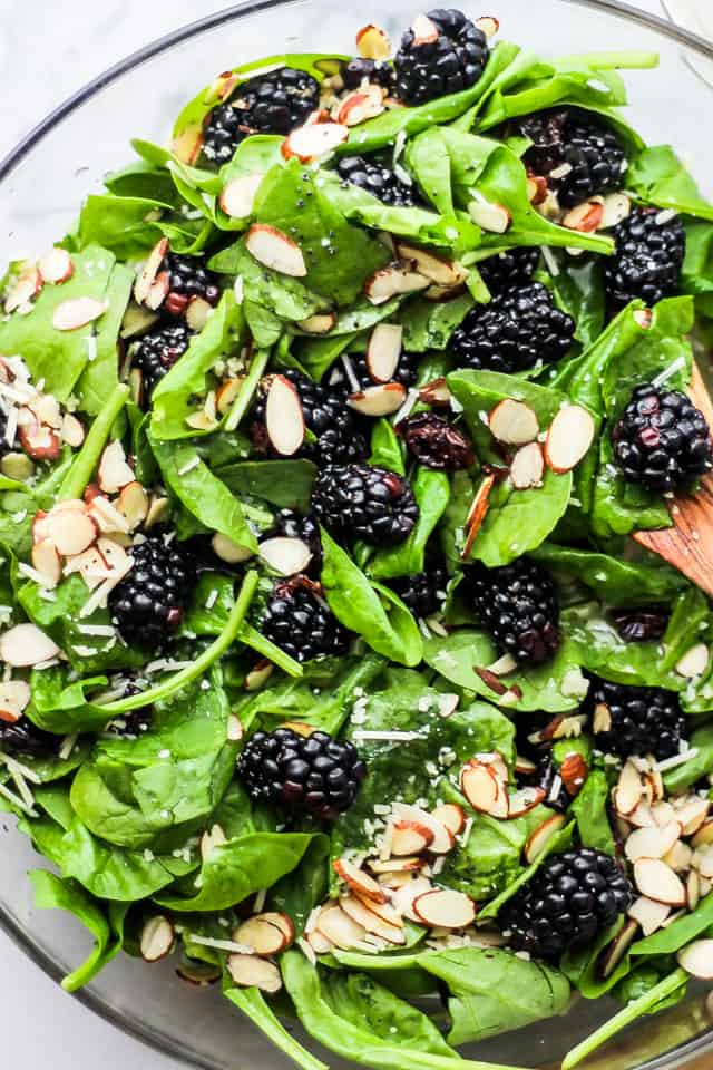 Spinach Salad with blackberries served in a clear glass salad bowl