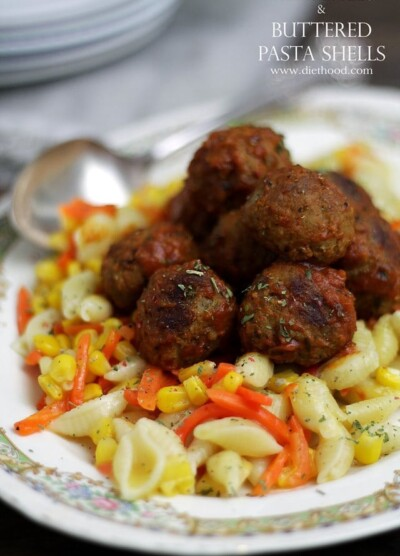 Meatballs on top of a plate of pasta, corn and carrots