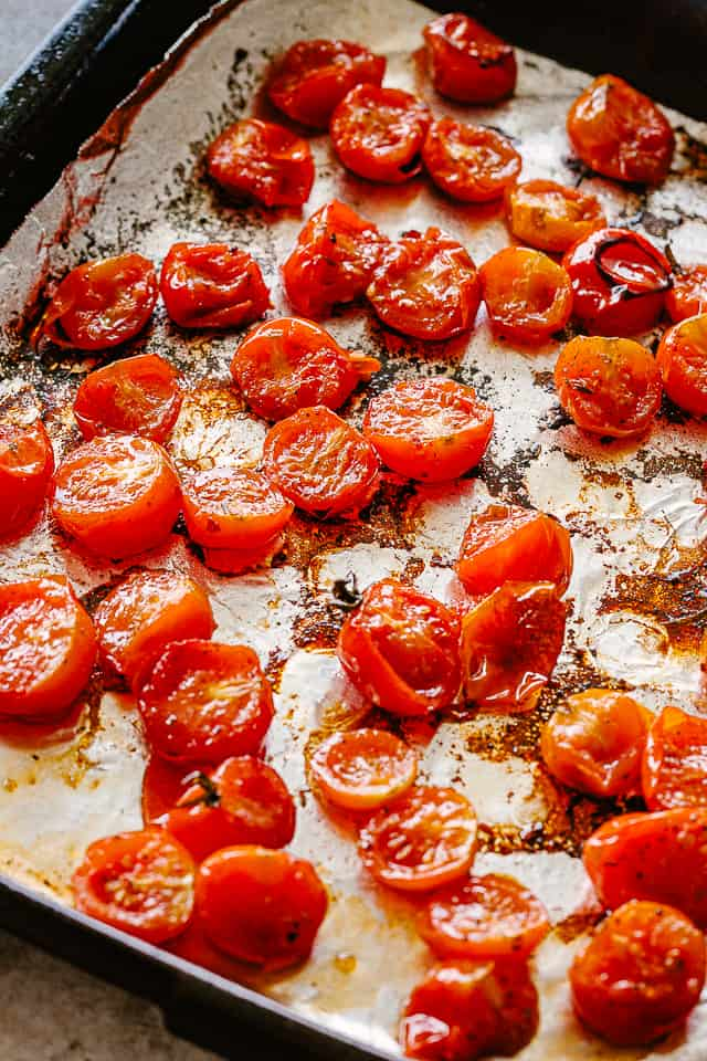 Roasted tomatoes on a baking sheet.