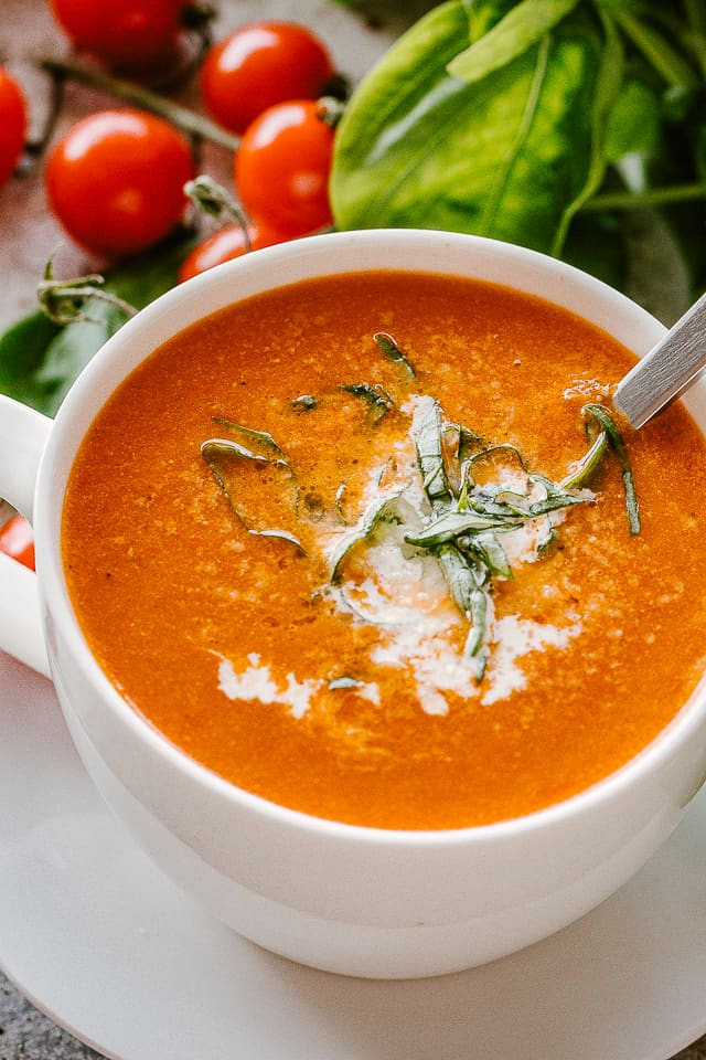 Bowl of Tomato Soup garnished with basil and parmesan cheese.
