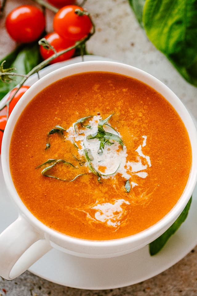 Bowl of Roasted Tomato Soup garnished with basil and parmesan cheese.