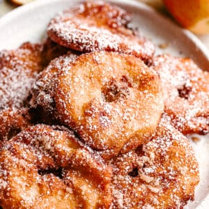 fried apple rings served on a white plate.