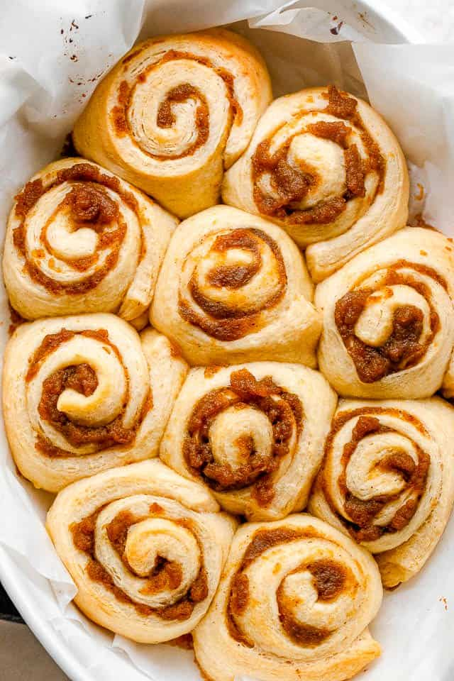 pumpkin pie cinnamon rolls arranged in a baking dish over parchment paper