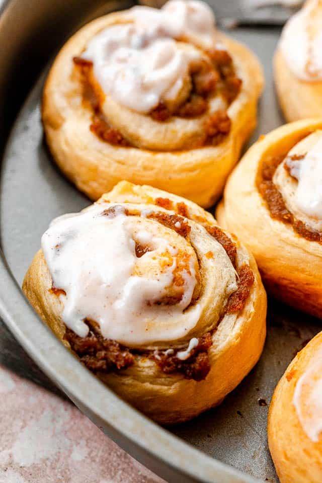 side shot of pumpkin pie cinnamon rolls in a cake pan