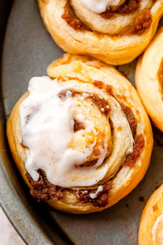close up shot of pumpkin pie cinnamon rolls iced with cream cheese frosting