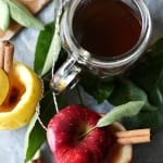 Spiked Apple Cider in a glass mug next to apples with cinnamon sticks