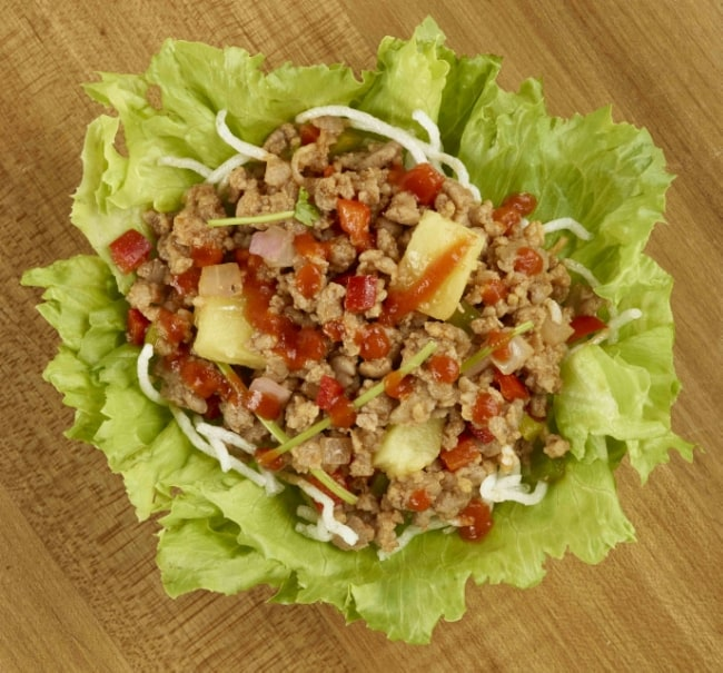 Top view of a lettuce bowl filled with ground pork and pineapple mixture and drizzled with sriracha sauce