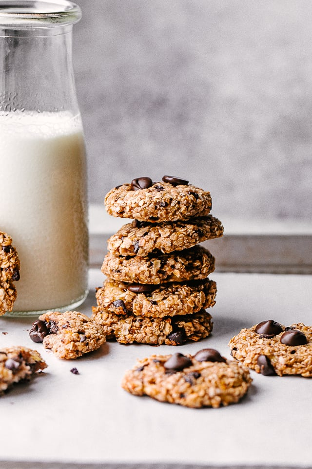 banana oats chocolate chip cookies stacked next to a milk jub