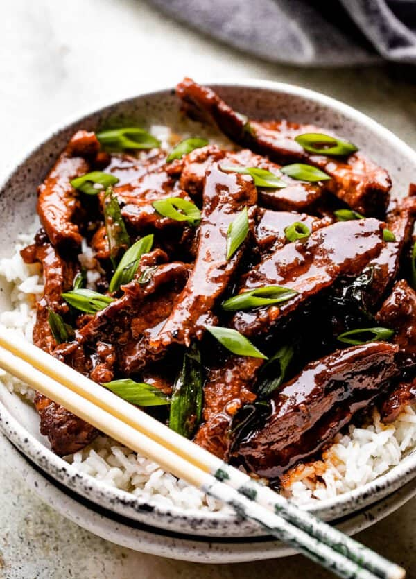 Mongolian beef served over rice on a white plate with chopsticks.