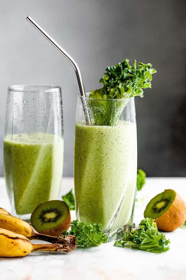 two tall drinking glasses with green smoothie