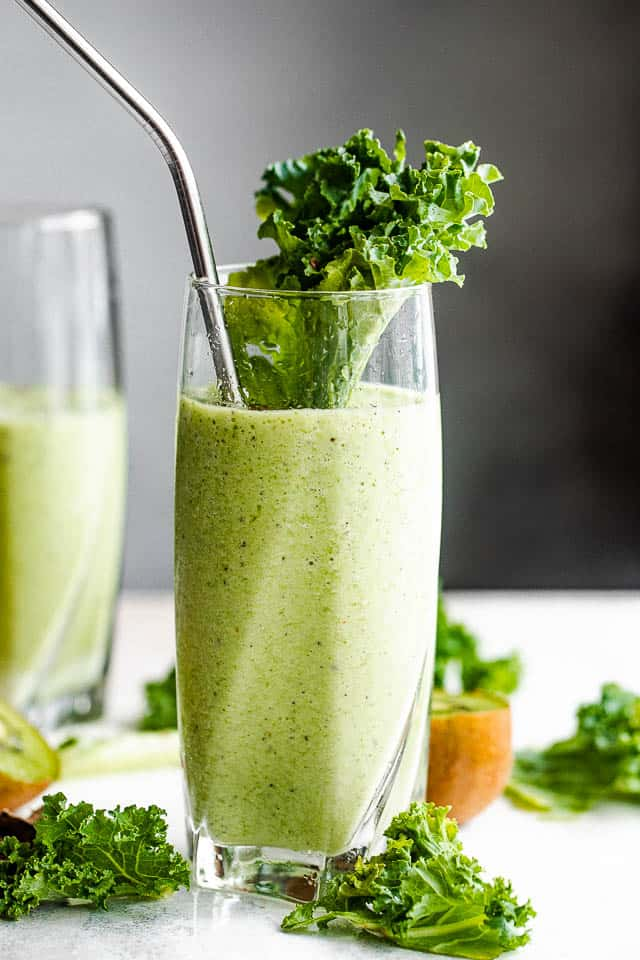 side shot of two tall drinking glasses with green smoothie
