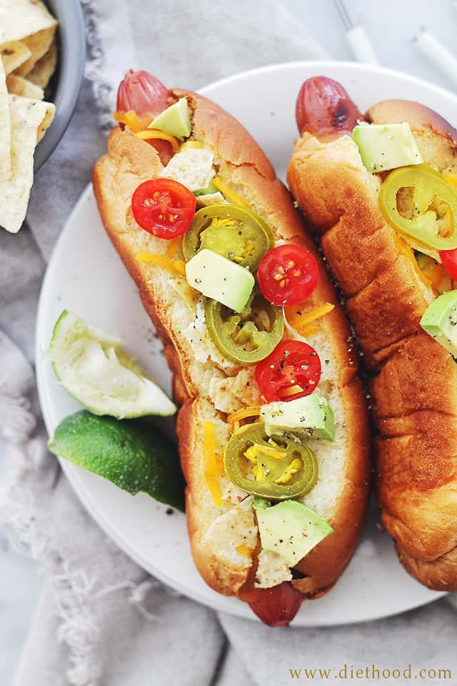 Hot Dogs in buns topped with sliced jalapenos, cheese, avocado, and tomatoes