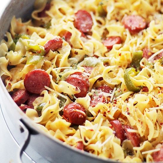 A pot filled with pasta and sausages