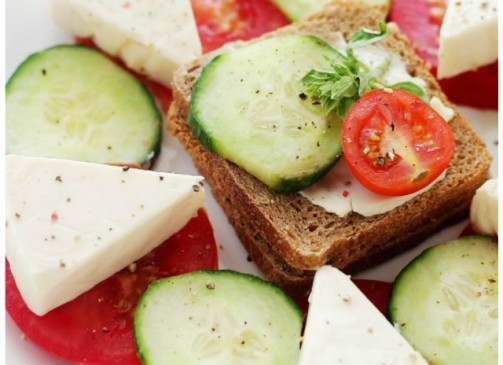 Tea Sandwiches - Flavorful whole-grain slice of bread topped with cheese wedges, cucumber slices and tomatoes.