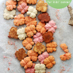 A bunch of different colored, pumpkin flavored spritz cookies on parchment paper