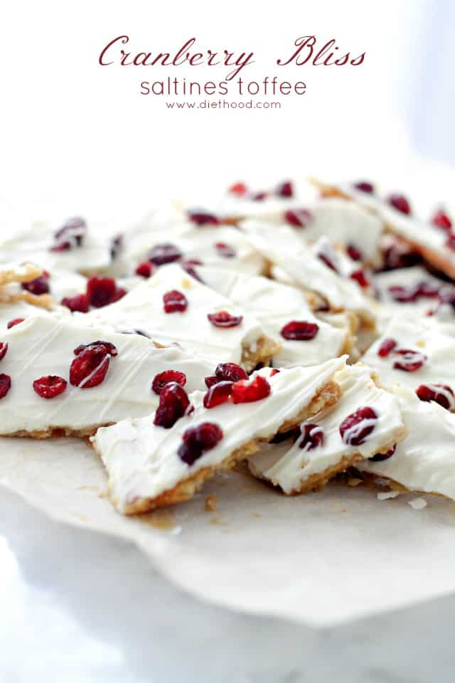 Saltine Crackers covered with sweet toffee, melted white chocolate and cranberries on a white surface