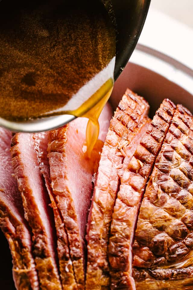 pouring honey mustard glaze over spiral cut ham