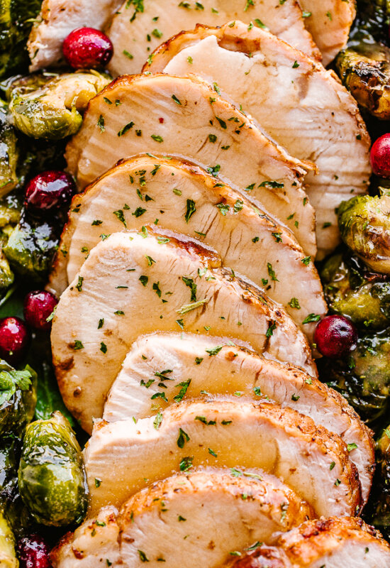 sliced turkey breast served alongside brussel sprouts.