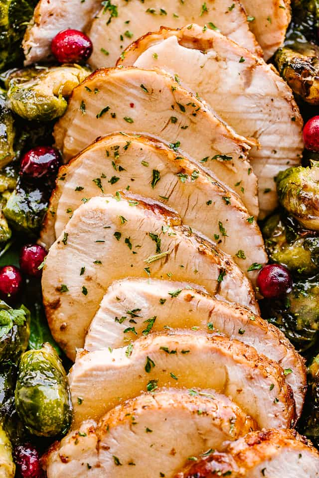 sliced turkey breast served alongside brussel sprouts.