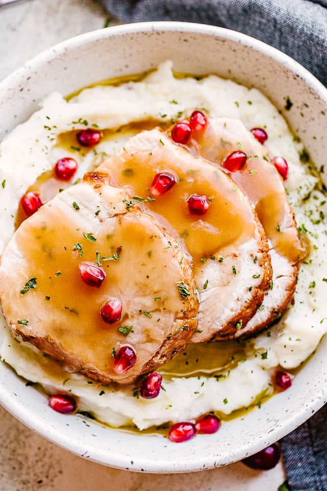sliced turkey breast served over mashed potatoes.