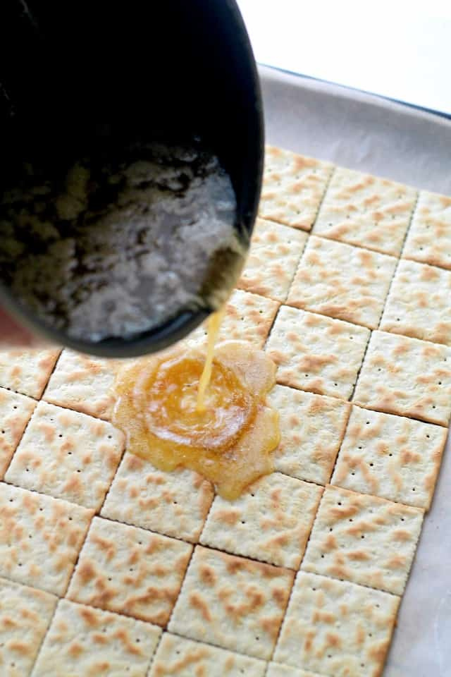 Toffee being poured onto Saltine Crackers