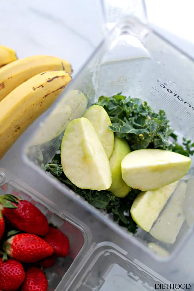 A container with fresh bananas, strawberries and cut green apples