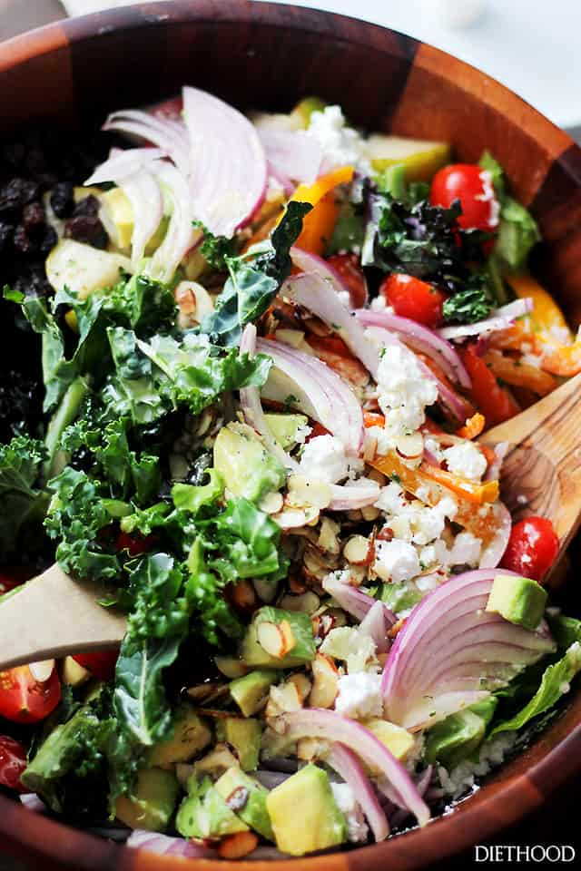 A wood bowl filled with kale, onions, feta, tomatoes, avocados, almonds and more