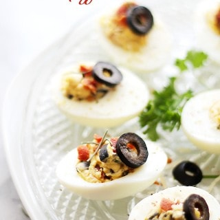 Bacon and Olives Deviled Eggs - The most delicious mixture of egg yolks, olives and bacon with sour cream, chives, and a sprinkle of cajun seasoning. Get the recipe on diethood.com