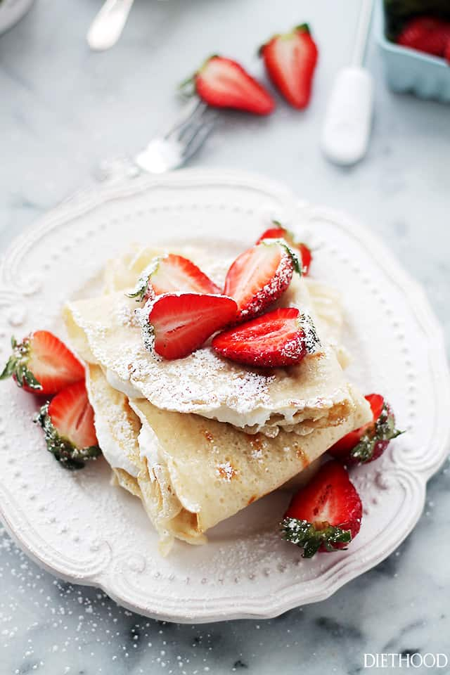 folded crepes filled with whipped cream and topped with strawberries