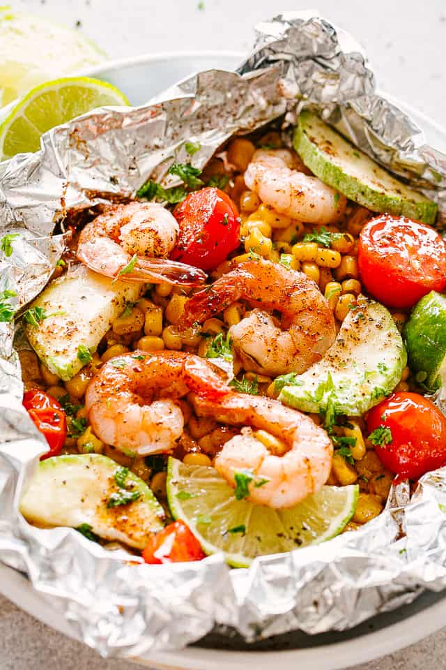 Foil packs with shrimp, corn, and zucchini.
