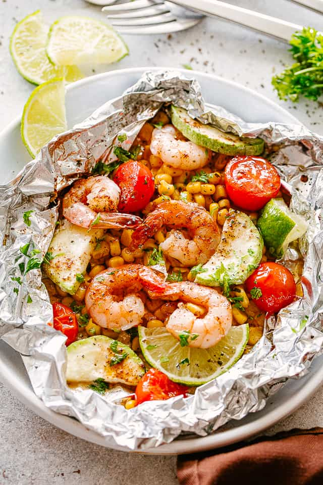 Grilled shrimp in foils on a plate.