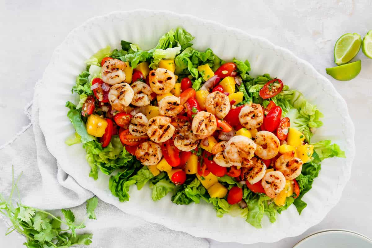 Overhead view of mango and shrimp salad on a white serving plate
