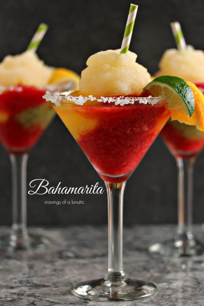 Red Bahamarita cocktail in a martini glass with a lime wedge