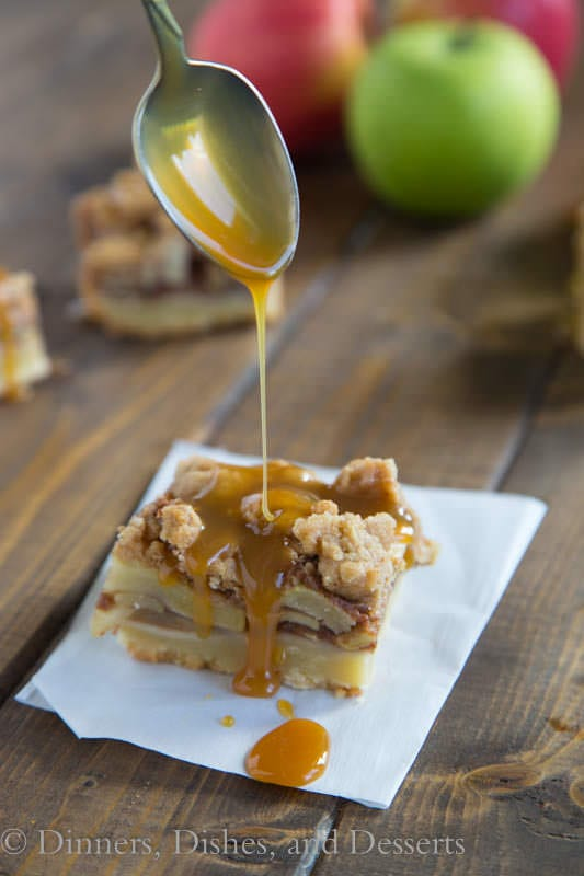 Caramel apple pie bar with caramel drizzle on a piece of parchment paper