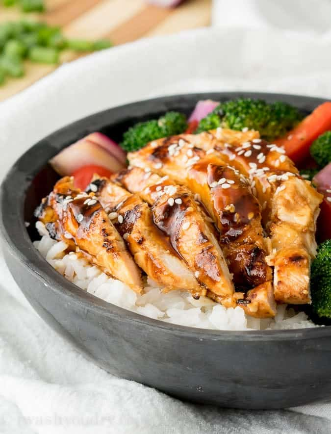Sliced teriyaki chicken with vegetables over rice in a bowl