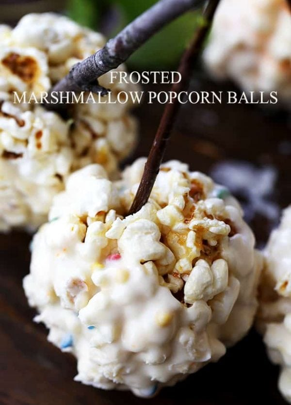 Frosted Marshmallow Popcorn Balls - Held together with a mixture of melted marshmallows and butter, and dipped in Frosting, these Marshmallow Popcorn Balls make great treats for kids, especially around Halloween!
