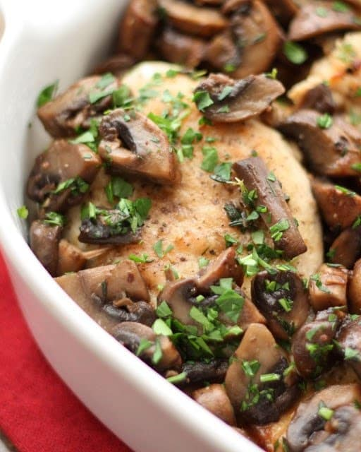 Chicken with Mushrooms in a serving bowl topped with fresh herbs
