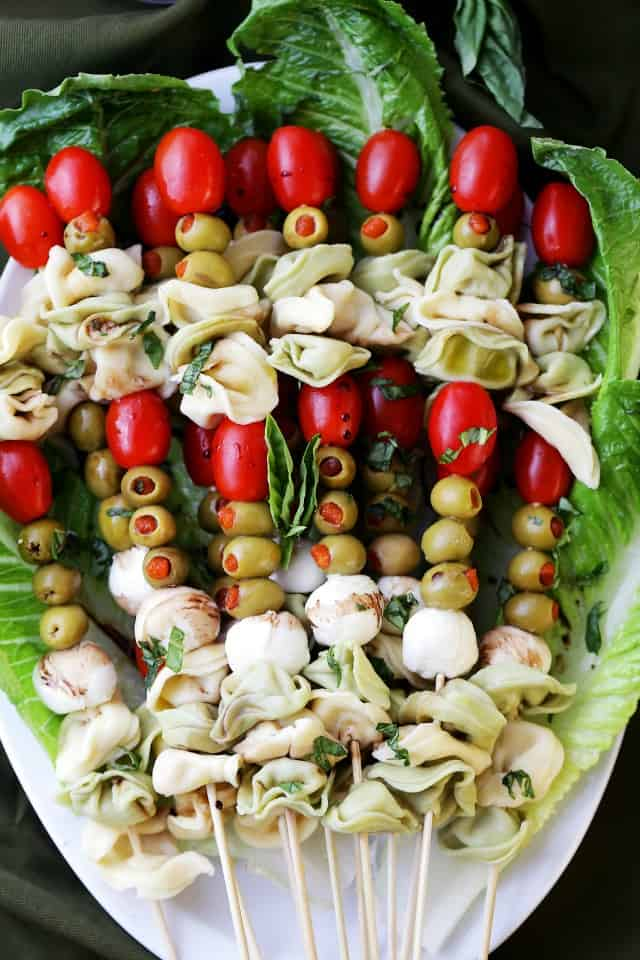 Tortellini Skewers with Olives Tomatoes and Cheese Recipe - Fun and festive appetizer plate with cheesy tortellini, flavorful manzanilla olives, grape tomatoes and fresh mozzarella cheese threaded on skewers. A gorgeous addition to your Holiday table!