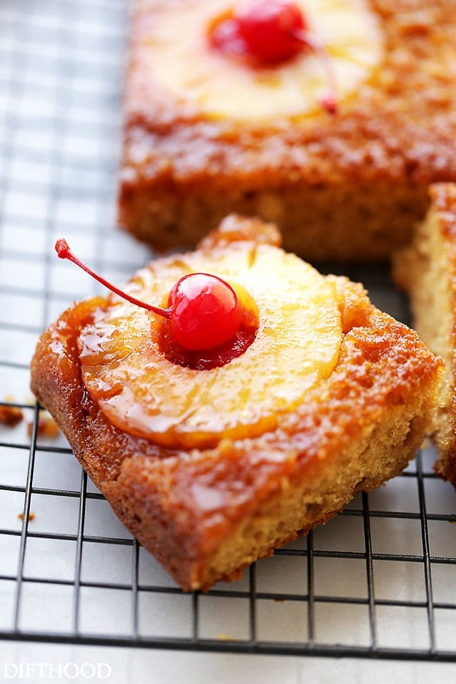 Pineapple Upside Down Cake topped with a cherry and pineapple on a wire rack