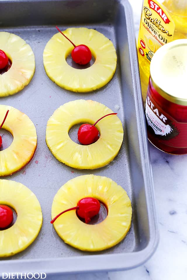 Pineapple rings and cherries laid out on a baking sheet
