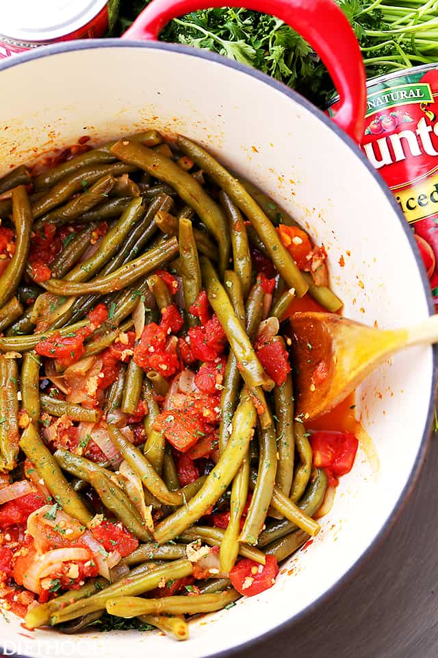 Green Beans and Tomatoes mixed together in a pot with a wooden spoon
