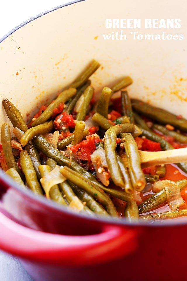 Green Beans and Tomatoes in a red pot being stirred with spoon
