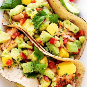 Salmon Tacos with Mango Avocado Salsa - Healthy, deliciously seasoned salmon tacos topped with an amazing mango avocado salsa and a cilantro-yogurt sauce.