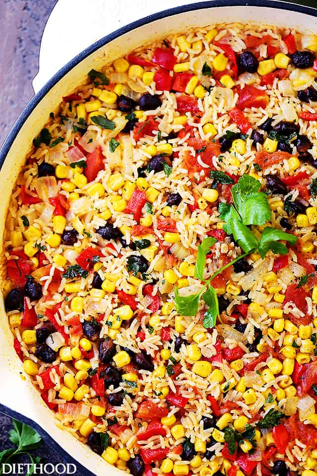 Fiesta Rice in a white skillet with black beans, tomatoes, and corn