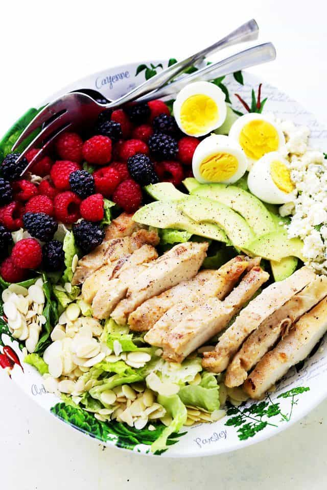 salad bowl filled with sliced chicken, raspberries, blackberries, halved hard boiled eggs, crumbled cheese, and nuts.